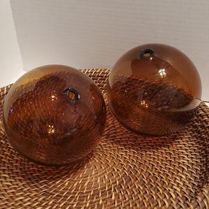 2 brown glass decorative orbs.